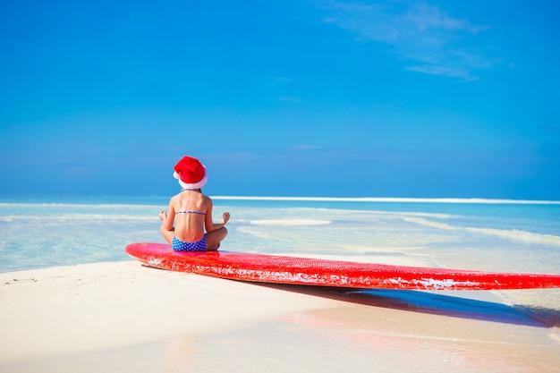 Petite fille mignonne en bonnet de noel sur la plage blanche pendant les vacances en position du lotus Photo Premium