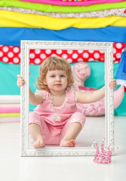 Petite fille mignonne dans un costume rose assis sur le sol et souriant sur un cadre blanc en bois. Photo Premium