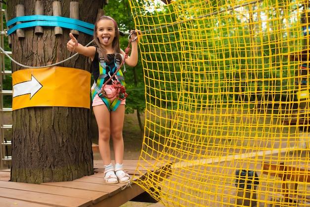 Petite fille mignonne exécute un parcours du combattant dans un parc de corde Photo Premium