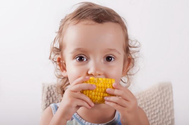 Petite fille mignonne frisée, manger du maïs assis sur la chaise. Photo Premium