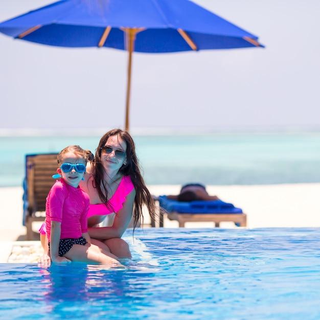 Petite fille mignonne et heureuse mère profitant de vacances dans une piscine en plein air Photo Premium