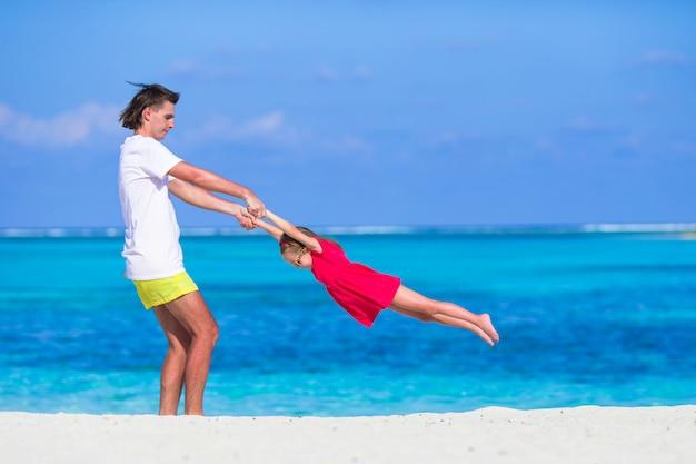Petite fille mignonne et papa pendant les vacances à la plage tropicale Photo Premium