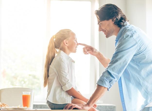 La petite fille mignonne et son beau père parlent. Photo Premium