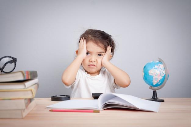 Petite fille mignonne souffrant de maux de tête tout en faisant du surmenage avec apprentissage Photo Premium