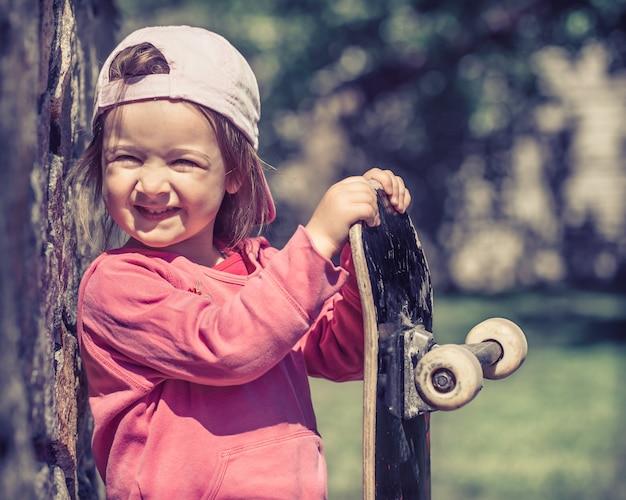 Une Petite Fille à La Mode Tient Une Planche à Roulettes Et Joue à L'extérieur, Les Belles émotions D'un Enfant. Photo gratuit