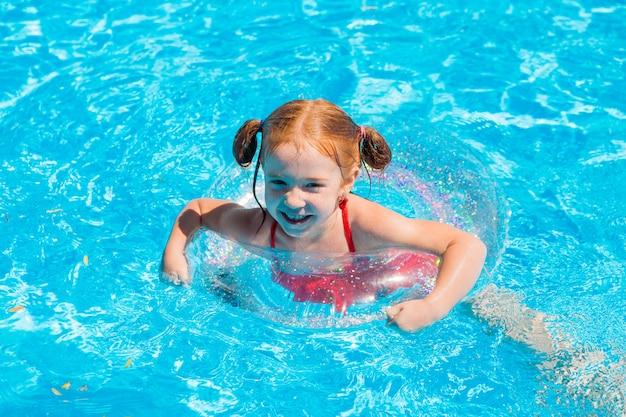 Petite fille nageant dans la piscine en été Photo Premium