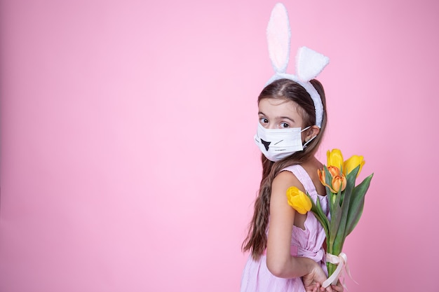 Petite Fille Avec Des Oreilles De Lapin De Pâques Et Portant Un Masque Médical Tient Un Bouquet De Tulipes Dans Ses Mains Sur Un Rose Photo gratuit