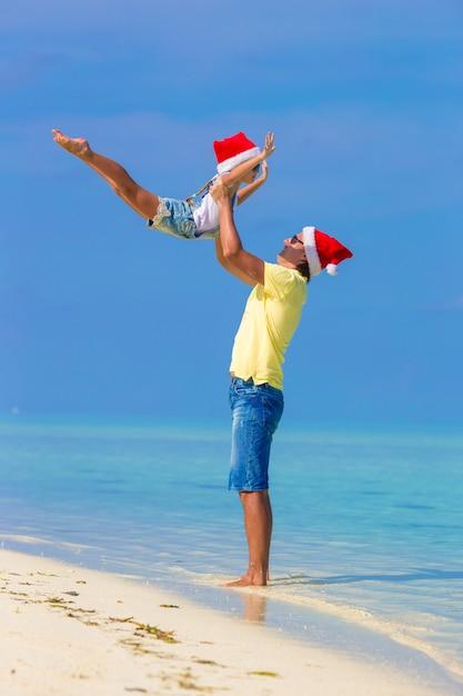 Petite fille et papa heureux à santa hat pendant les vacances à la plage Photo Premium