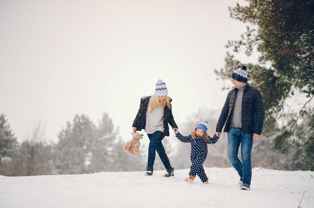 Petite fille avec des parents jouant dans un parc d'hiver Photo gratuit