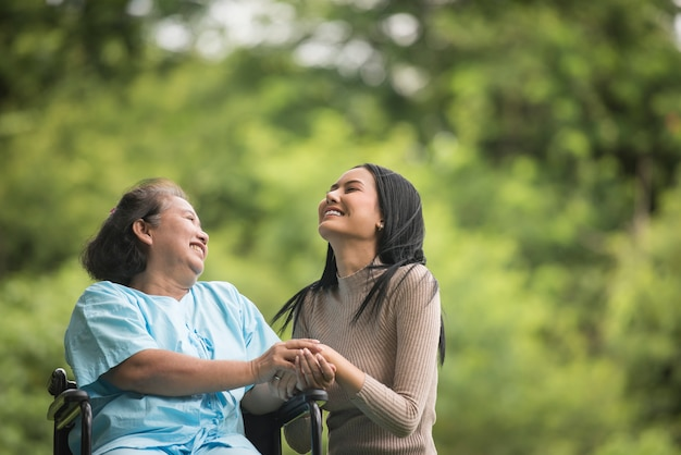 Petite-fille Parle Avec Sa Grand-mère Assise Sur Un Fauteuil Roulant, Concept Joyeux, Famille Heureuse Photo gratuit
