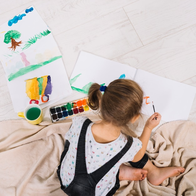 Petite fille peignant avec aquarelle au sol Photo gratuit