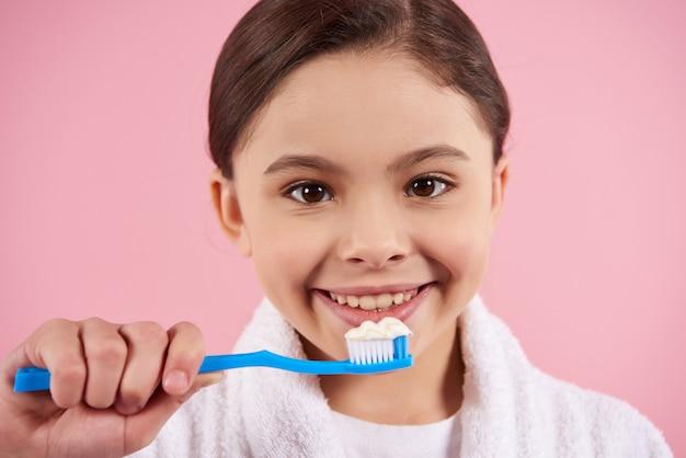 Petite fille en peignoir se brosse les dents Photo Premium