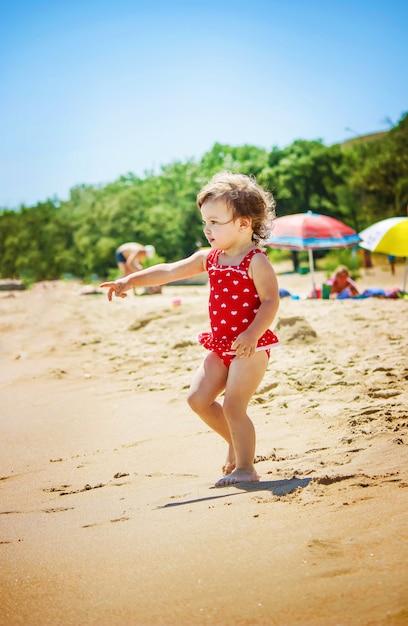 Petite fille sur la plage, au bord de la mer mise au point sélective. Photo Premium