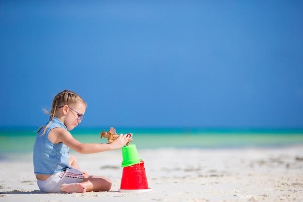 Petite fille à la plage blanche tropicale faisant le château de sable Photo Premium