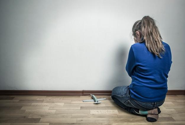 Petite Fille En Pleurs Assis Dans Une Pièce Vide. L'enfant Est Offensé. Autisme Photo Premium