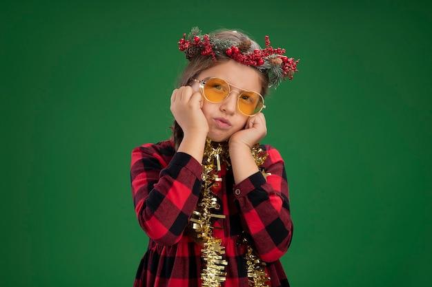 Petite Fille Portant Une Couronne De Noël En Robe à Carreaux Avec Guirlandes Autour Du Cou Regardant La Caméra Avec Une Expression Confuse Avec Les Mains Sur Son Visage Debout Sur Fond Vert Photo gratuit