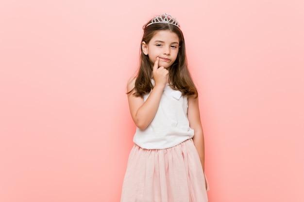 Petite fille portant un regard de princesse regardant de côté avec une expression douteuse et sceptique. Photo Premium