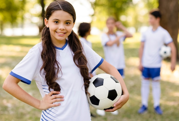 Petite Fille Posant Avec Un Ballon De Football à L'extérieur Photo gratuit