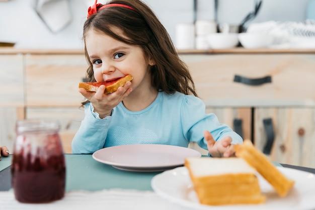 Petite fille prend son petit déjeuner Photo gratuit