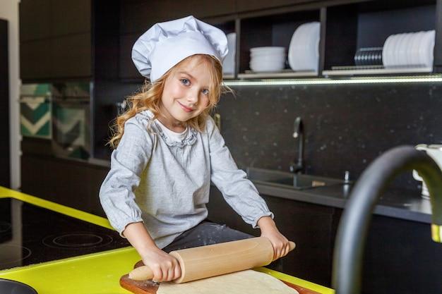 Petite fille prépare la pâte, cuire la tarte aux pommes maison de vacances dans la cuisine Photo Premium