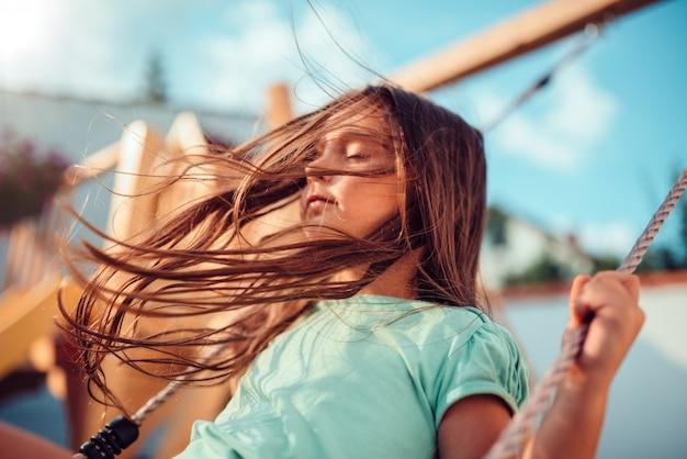 Petite fille profitant de la balançoire avec les yeux fermés et les cheveux longs volant Photo Premium