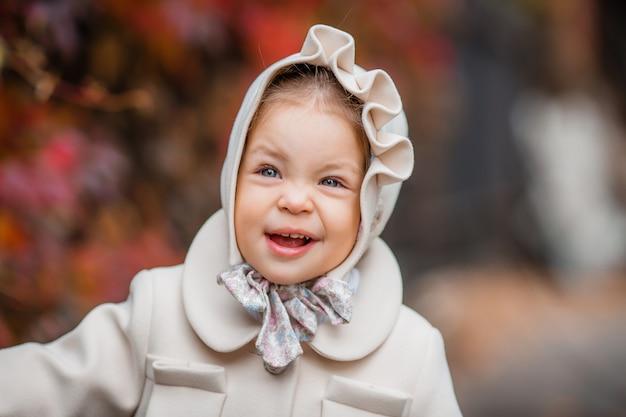 Petite fille sur une promenade dans le parc en automne Photo Premium
