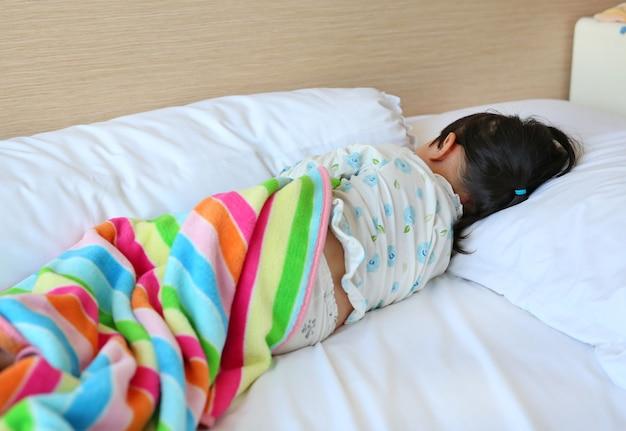 Petite fille en pyjama dormant sur le lit avec une couverture Photo Premium