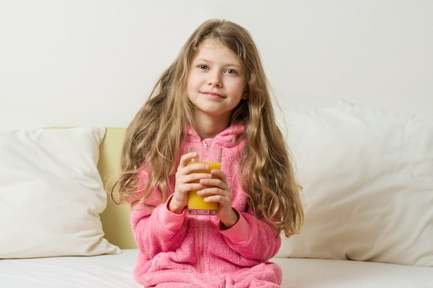 Petite fille en pyjama avec un verre de jus d'orange Photo Premium