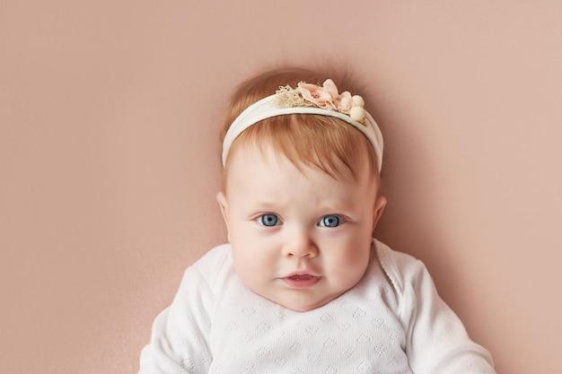 Petite fille de quatre mois se trouve sur un mur rose pâle Photo Premium