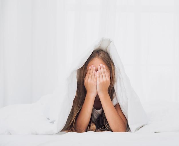 Petite fille qui couvre ses yeux Photo gratuit