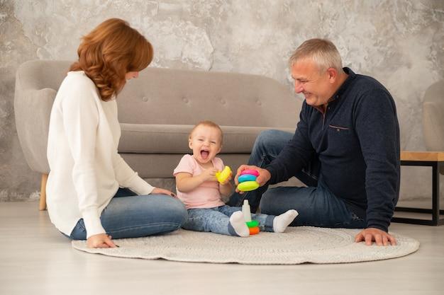 Petite Fille Recueille Une Pyramide Avec Ses Grands-parents Au Salon. La Famille Passe Du Temps Ensemble à L'intérieur, Livestile Photo Premium