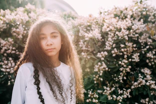 Petite fille regardant la caméra se tenant contre un champ de fleurs Photo gratuit