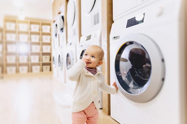 Petite fille regardant une machine à laver Photo Premium