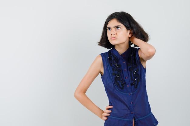 Petite Fille Regardant Tout En Se Grattant La Tête En Chemisier Bleu Et à L'hésitation. Photo gratuit