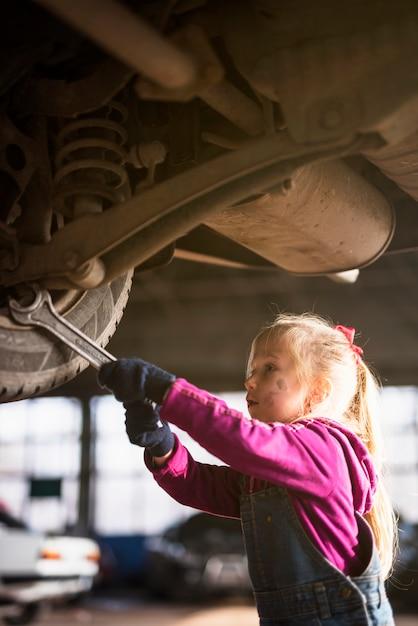 Petite fille en réparation de voiture avec clé Photo gratuit