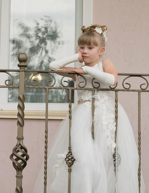 Petite fille en robe de bal sur le balcon Photo Premium