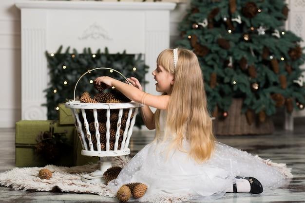 Petite fille en robe blanche joue avec des pommes de pin dans les décorations de noël Photo Premium