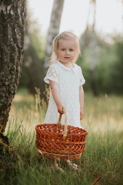 Petite fille en robe blanche avec un panier dans le parc. belle petite fille marchant dans un jardin ensoleillé avec un panier. Photo Premium