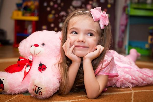Petite fille en robe rose se trouve sur le sol avec un jouet Photo Premium