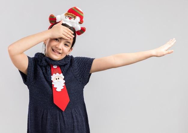 Petite Fille En Robe En Tricot Portant Une Cravate Rouge Avec Jante De Noël Drôle Sur La Tête Heureuse Et Positive Avec La Main Sur Son Front Souriant Joyeusement Photo gratuit