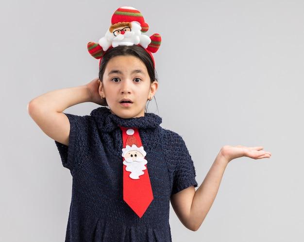 Petite Fille En Robe En Tricot Portant Une Cravate Rouge Avec Jante De Noël Drôle Sur La Tête Lookign Confondu Avec Le Bras Photo gratuit