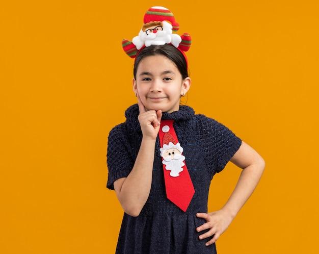Petite Fille En Robe En Tricot Portant Une Cravate Rouge Avec Une Jante De Noël Drôle Sur La Tête à La Recherche Avec Une Expression Sceptique Photo gratuit