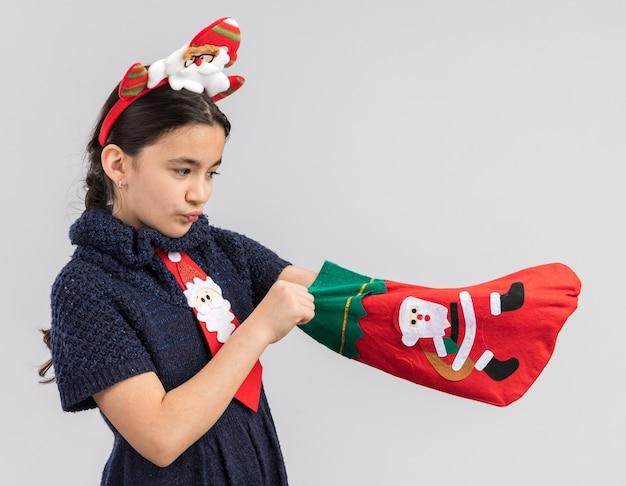 Petite Fille En Robe En Tricot Portant Une Cravate Rouge Avec Jante De Noël Drôle Sur La Tête Tenant Des Bas De Noël à La Recherche D'intrigué Photo gratuit