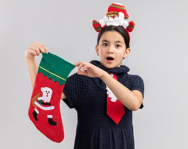 Petite Fille En Robe En Tricot Portant Une Cravate Rouge Avec Jante De Noël Drôle Sur La Tête Tenant Des Bas De Noël à La Surprise Photo gratuit