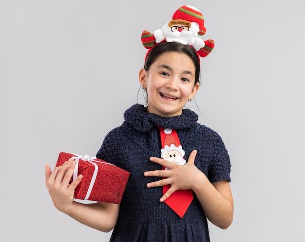 Petite Fille En Robe En Tricot Portant Une Cravate Rouge Avec Jante De Noël Drôle Sur La Tête Tenant Un Cadeau De Noël à Sourire Joyeusement Se Sentir Reconnaissant Photo gratuit
