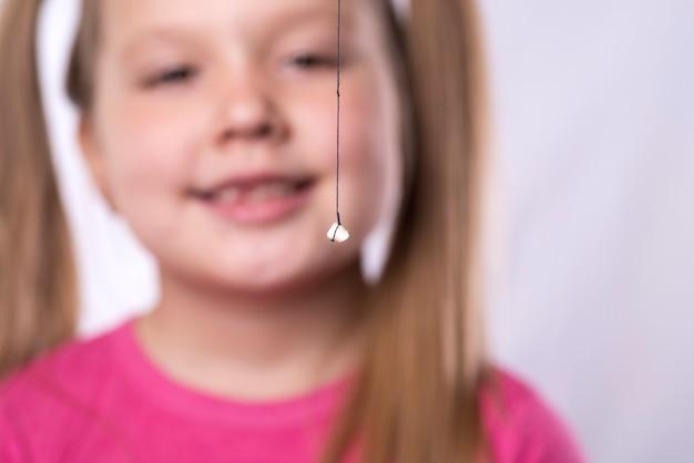 Petite Fille En Rose Tient Une Dent De Lait Sur Un Fil Photo Premium