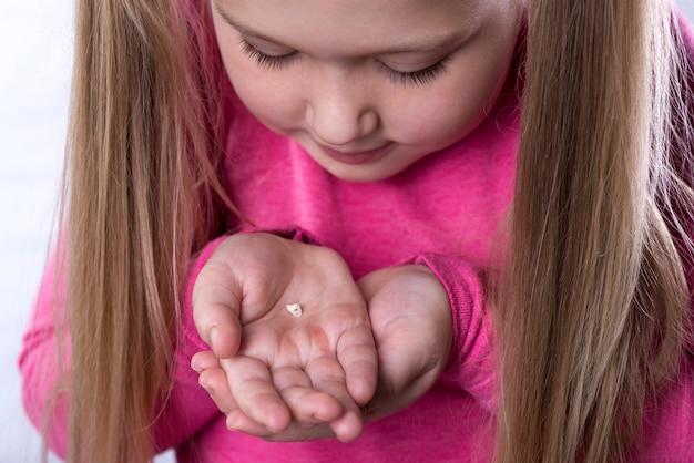 Petite Fille En Rose Tient Une Dent De Lait Tombée Dans Ses Paumes Photo Premium