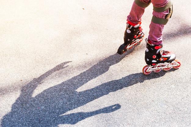 Une petite fille roule sur des rouleaux rouges sur l'asphalte Photo Premium