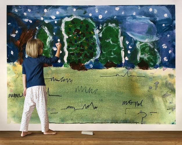 Petite fille s'amusant à dessiner sur un mur Photo Premium
