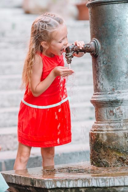 Petite Fille S'amusant Avec De L'eau Potable à La Fontaine De La Rue à Rome, Italie Photo Premium